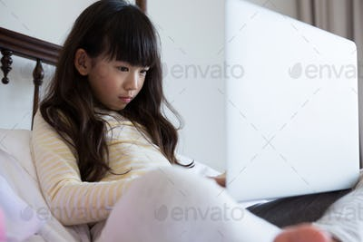 Girl with long hair using laptop on bed