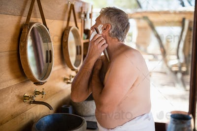 Man shaving his beard with razor in cottage