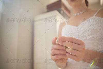 Midsection of bride holding earring at home