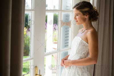 Side view of beautiful bride looking through window at home