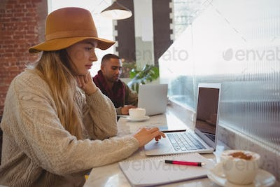 Businesswoman using laptop at counter