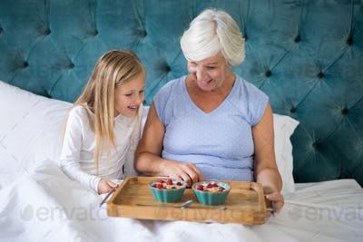 Smiling granddaughter and grandmother having breakfast on bed