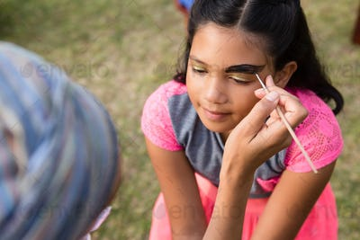 Cropped image of woman doing face paint on girl