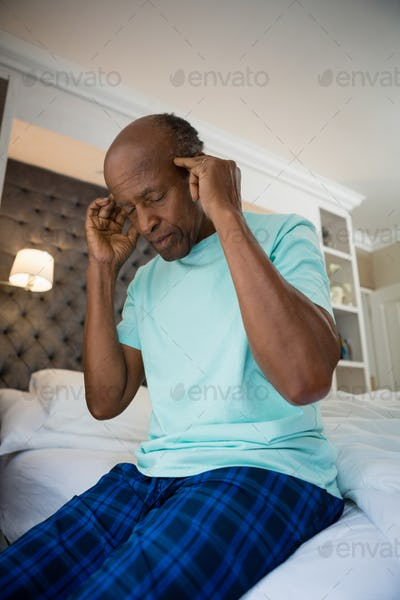 Low angle view of senior man suffering from headache at home