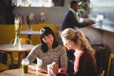 Smiling female friends using tablet computer at coffee shop