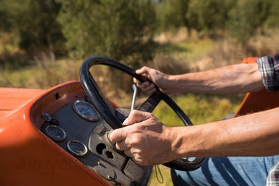Mid section of man driving tractor in olive farm