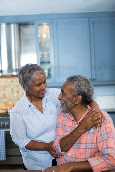 Happy couple talking in kitchen