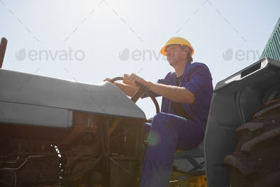 Attentive worker driving a tractor