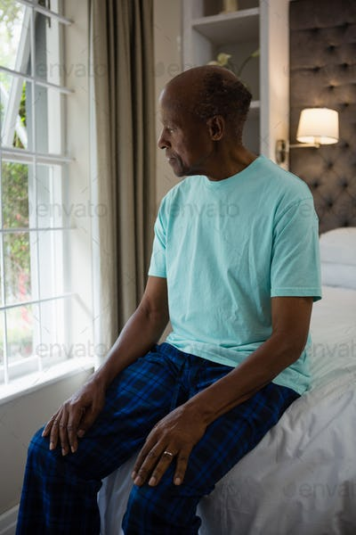 Thoughtful senior man sitting on bed by window