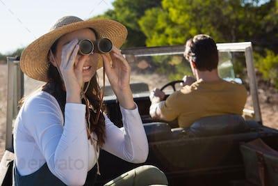Woman using binocular with man driving off road vehicle