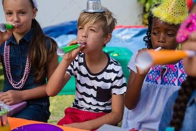 Children blowing part horns