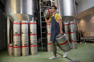 Full length of worker with kegs walking at warehouse