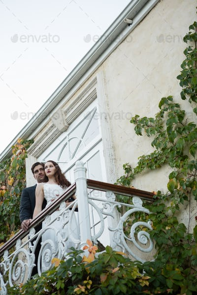 Low angle view of couple embracing while standing in balcony