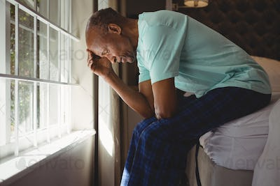 Side view of serious senior man sitting on bed by window