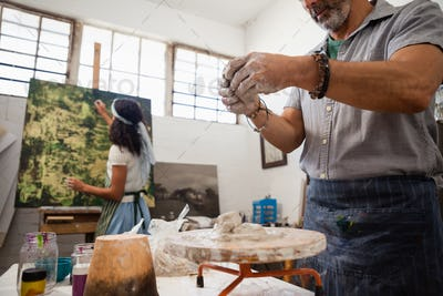 Man molding clay while woman painting on canvas