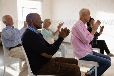 Smiling senior people applauding while sitting on chair