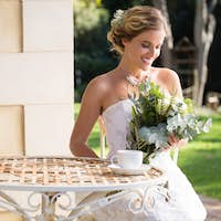 Beautiful bride looking at bouquet while sitting on chair