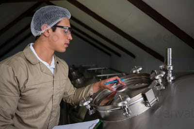Worker examining storage tank