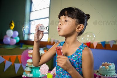 Girl playing with bubble wand during birthday party