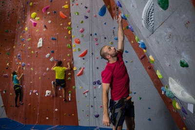 Dedicated athletes and trainer climbing wall in club