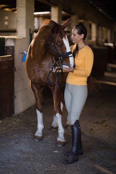 female jockey with horse standing in stable