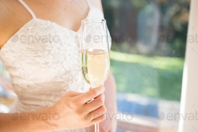 Midsection of bride holding champagne while standing by window