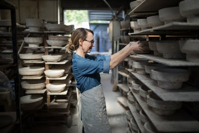 Female potter placing bowl in shelf