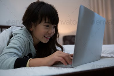 Smiling girl using laptop on bed