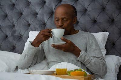Senior man having breakfast on bed