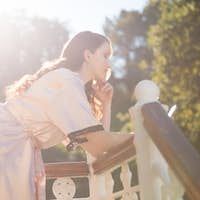 Bride using mobile phone while leaning on railing in balcony