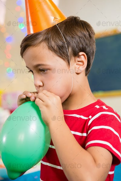 Cute boy blowing balloon during birthday party