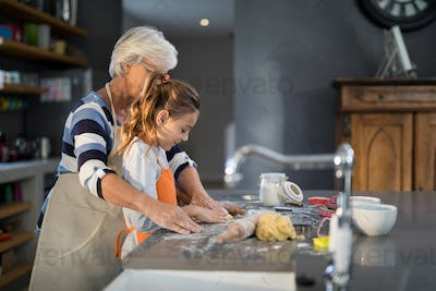 Grandmother helping granddaughter to flatten dough