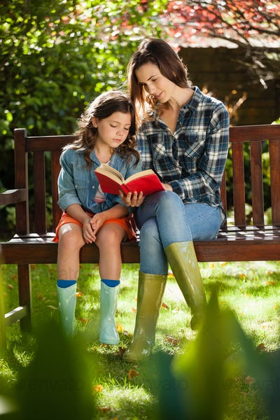 Mother reading book to daughter while sitting on wooden bench