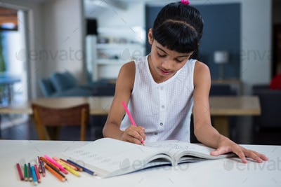 Girl drawing in book on counter
