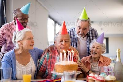 Friends looking at senior man blowing birthday candles