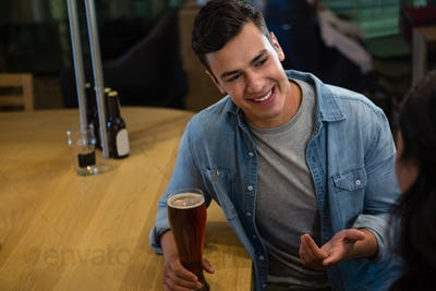 Smiling man talking to friend at bar