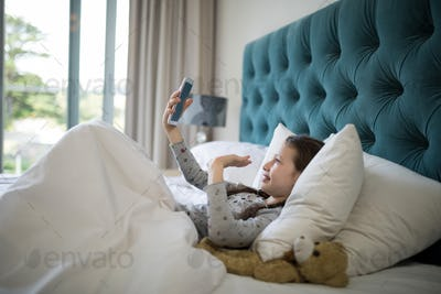 Girl video calling on mobile phone in bedroom