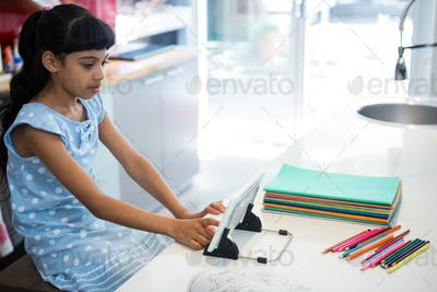 High angle view of girl using digital tablet by colored pencils on kitchen counter
