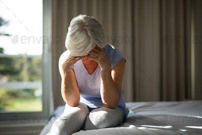 Tense senior woman sitting on bed in bedroom