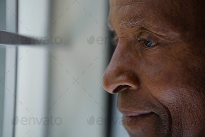 Close up of thoughtful senior man looking out through window