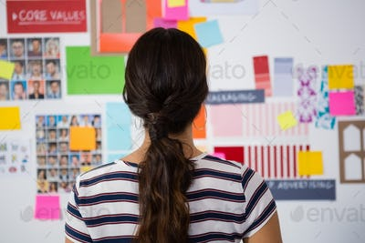 Rear view of businesswoman against sticky notes in office
