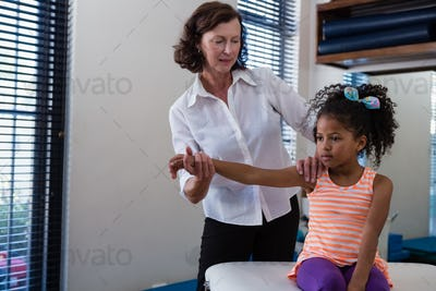 Physiotherapist giving hand massage to a girl