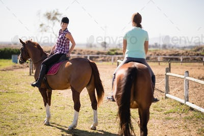 Female friends horseback riding on field