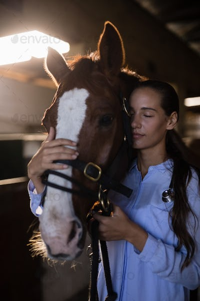 Female vet with eyes closed standing by horse at stable