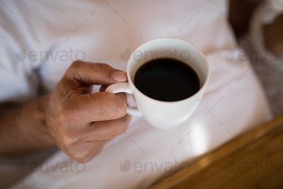 Mid section of man having black coffee