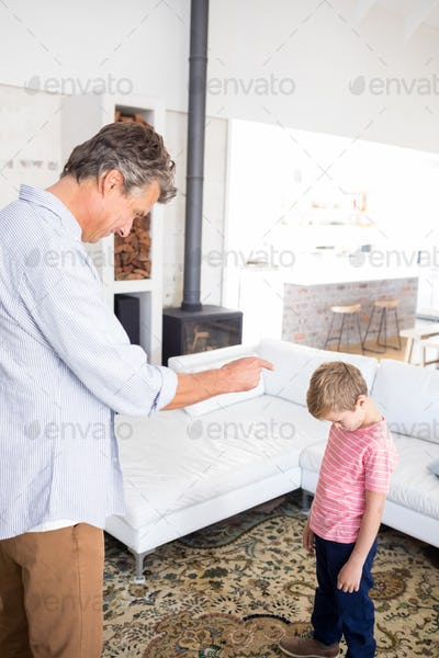Angry father scolding his son in living room