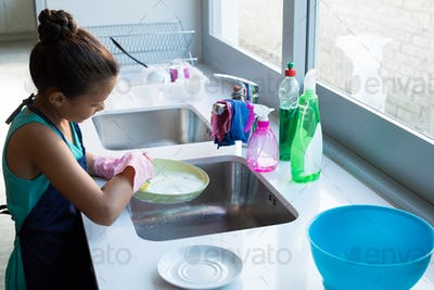 Cute little girl washing plate in kitchen sink