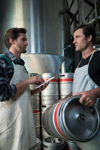 Coworkers discussing while examining kegs