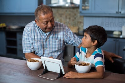 Grandfather and grandson using tablet computer during breakfast