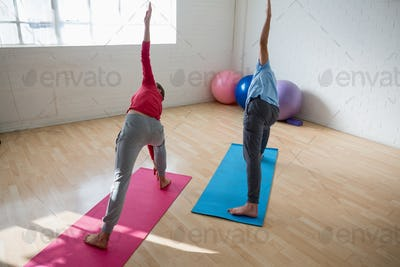Instructor with female student practicing triangel pose in yoga studio